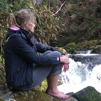 Cara Wilde sitting meditating by a river