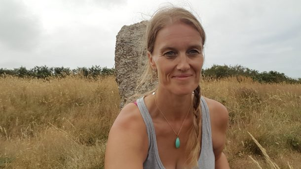 cara wilde wearing grey vest top and ble stone necklace sitting in front of stone circle with long brown grass